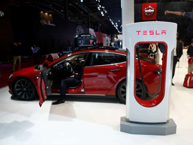 A charging plug sits attached to a Tesla Model S automobile, produced by Tesla Motors Inc., at the Paris Motor Show.