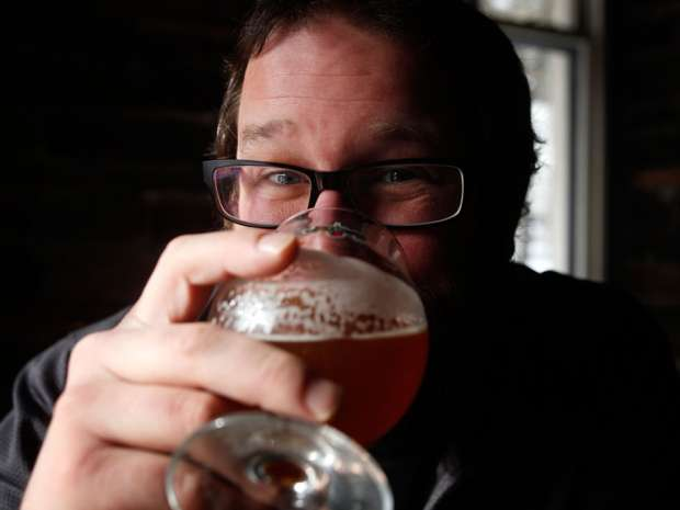 Steve Beauchesne co-founder of Beau's All Natural Brewing co. holds a glass of Beau's beer. Beau's has announced it will reward employees who've been with the brewery for more than 12 months with a single share in the well known organic brewer.
