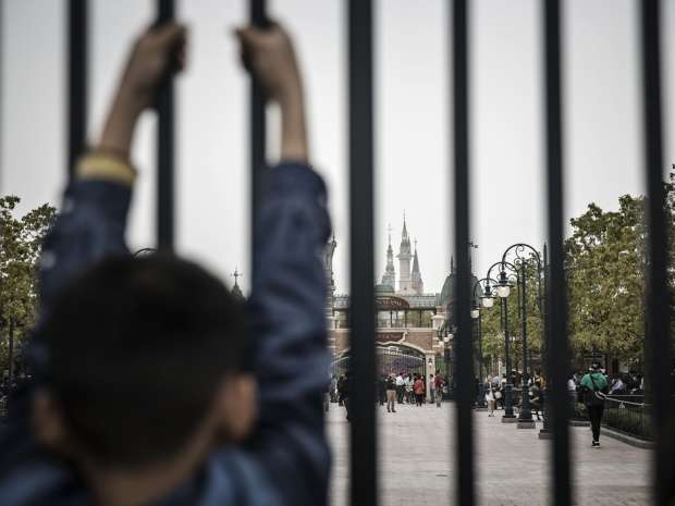 A child holds onto a gate at the Walt Disney Co.'s Disneyland Resort in Shanghai, China, on Saturday, May 7, 2016.