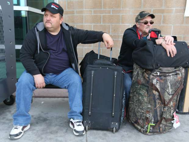 Rodney Stuckey, left, and Clarence Andrews (both from Newfoundland) who worked at the Syncrude site wait for a cab at the evacuee reception area in Calgary. The college is temporarily housing Ft McMurray evacuees.
