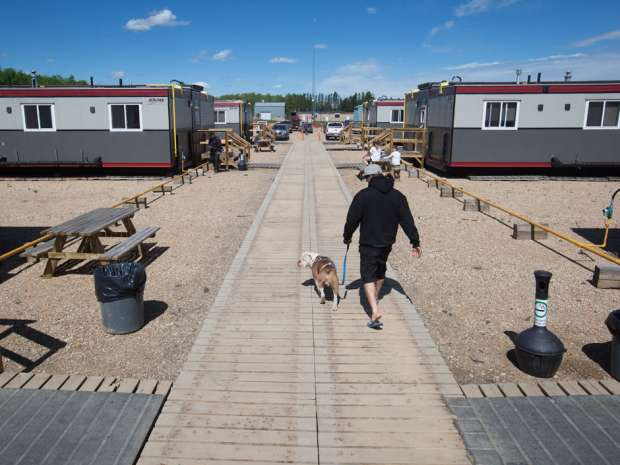 A Fort McMurray wildfire evacuee walks a co-worker's dog at an oilfield work camp where approximately 500 evacuees are staying, in Wandering River, Alberta. Oilsands companies plan to move workers in and out of the region through temporary workforce arrangements from Calgary and Edmonton to help restart operations.
